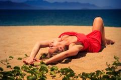la muchacha rubia de la visión superior en mentiras rojas del vestido en la arena dobla la rodilla Imagenes de archivo