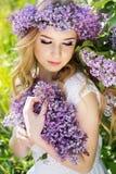 La muchacha rubia de ojos azules con la guirnalda de la lila florece Fotos de archivo libres de regalías