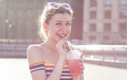 La muchacha rubia de la sonrisa hermosa de los jóvenes en una calle de la ciudad en un día soleado bebe una ensalada de fruta de  Fotos de archivo