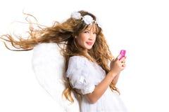 La muchacha rubia del ángel con el teléfono móvil y la pluma se va volando en blanco Imagen de archivo libre de regalías