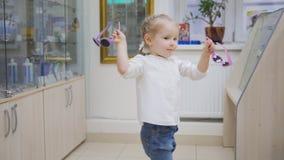 La muchacha rubia del niño adorable en clínica de la oftalmología juega en pasillo cerca de tienda de los vidrios fotografía de archivo