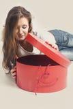 La muchacha hermosa mira en una caja roja y redonda Foto de archivo