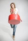 La muchacha hermosa mira en una caja roja y redonda Fotografía de archivo libre de regalías