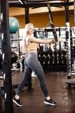 La muchacha rubia delgada con el pelo largo tiene un entrenamiento de TRX en el gimnasio moderno por completo de la luz del sol fotografía de archivo