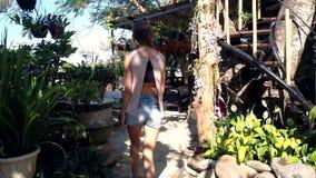 La muchacha rubia delgada de la vista lateral en pantalones cortos entra en el café abierto del templo almacen de metraje de vídeo