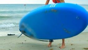 La muchacha rubia delgada toma el tablero de paleta de goma camina al océano metrajes