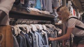 La muchacha rubia elige cosas en la tienda de la ropa de las mujeres almacen de video