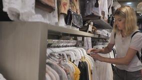 La muchacha rubia elige cosas en la tienda de la ropa de las mujeres almacen de metraje de vídeo