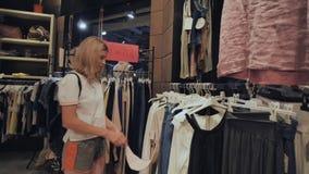La muchacha rubia elige cosas en la tienda de la ropa de las mujeres metrajes