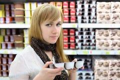 La muchacha rubia elige el yogur en almacén Fotos de archivo
