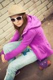 La muchacha rubia en casquillo y gafas de sol se sienta en un monopatín Fotos de archivo libres de regalías