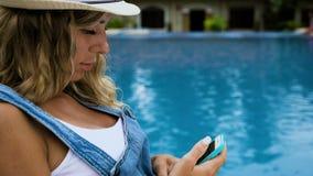 La muchacha rubia en el sombrero, guardapolvos miente por la piscina y mira para llamar por teléfono almacen de video