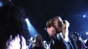 La muchacha rubia en el top del negro, vidrios baila en partido en club nocturno entre otras personas proyectores muchedumbre almacen de video