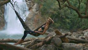 La muchacha rubia en hamaca sobre registros acerca a la cascada
