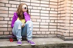 La muchacha rubia en las gafas de sol se sienta en su monopatín Fotografía de archivo