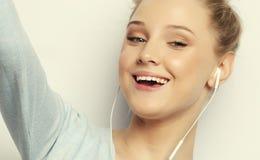 La muchacha rubia en la música que escucha de los auriculares que toma la foto hace autorretrato en llevar del smartphone la ropa Foto de archivo