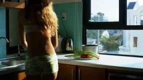 La muchacha rubia en pantalones cortos pone verduras en la tabla almacen de video