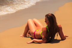 La muchacha rubia en parte trasera del primer del bikini miente encendido detrás por el mar Foto de archivo