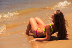 La muchacha rubia en parte trasera del primer del bikini miente encendido detrás por el mar Imagen de archivo libre de regalías