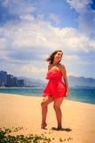 la muchacha rubia en rojo baila descalzo en el pelo largo de las sacudidas del viento de la arena Imágenes de archivo libres de regalías