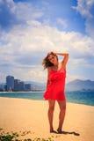 la muchacha rubia en soportes rojos en la playa alisa sacudido por el pelo del viento Fotos de archivo libres de regalías