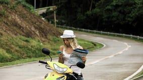 La muchacha rubia en un sombrero, se sienta en una bici y mira el teléfono y un mapa, mira la ruta en Asia metrajes