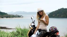 La muchacha rubia en un sombrero, se sienta en una bici y mira el teléfono y un mapa, mira la ruta en Asia almacen de video