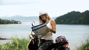 La muchacha rubia en un sombrero, se sienta en una bici y mira el teléfono y un mapa, mira la ruta en Asia almacen de metraje de vídeo