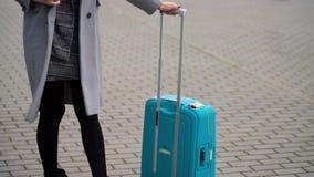 La muchacha rubia en una capa gris con una maleta se coloca cerca del terminal de aeropuerto almacen de video