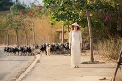 la muchacha rubia en vietnamita viste soportes contra multitud Imagenes de archivo