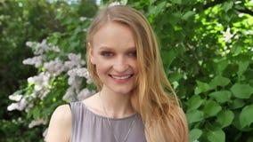 La muchacha rubia encantadora joven está mirando en la cámara en parque en d3ia en el verano, sonriendo almacen de video