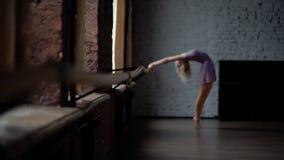 La muchacha rubia entrena a su desviación cerca de ventana almacen de metraje de vídeo