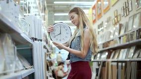 La muchacha rubia está admitiendo las manos embala con el reloj de pared en un hipermercado almacen de metraje de vídeo