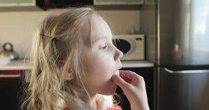 La muchacha rubia está comiendo una torta blanca en la cocina metrajes