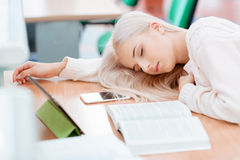 La muchacha rubia está durmiendo en el escritorio Fotografía de archivo libre de regalías