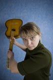 La muchacha rubia está enojada quiere luchar con la guitarra Imagen de archivo libre de regalías