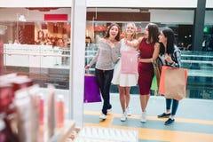 La muchacha rubia está mirando delantera y el señalar Ella es muy emocionada Otras muchachas están mirando en la misma dirección  foto de archivo libre de regalías