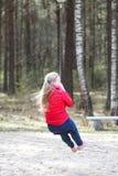 La muchacha rubia feliz del adolescente se vistió en chaqueta roja y los tejanos que saltaban y que montaban abajo con el amortig Imagen de archivo