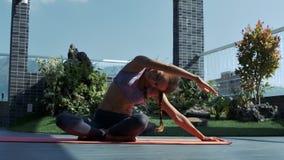 La muchacha rubia fija actitud de la yoga en tejado debajo del cielo