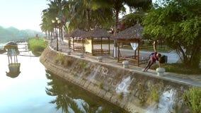 La muchacha rubia hace aptitud en orilla del río con las palmas almacen de video