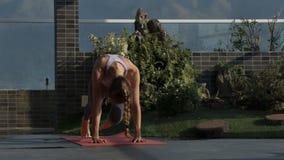 La muchacha rubia hace ejercicio de la yoga en terraza del tejado