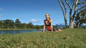 La muchacha rubia hace yoga en hierba contra paisaje