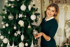 La muchacha rubia hermosa adorna un árbol de navidad con los juguetes Imagen de archivo