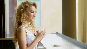 La muchacha rubia hermosa bebe una taza de café o de té caliente en café almacen de video
