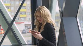 La muchacha rubia hermosa cerca de una ventana brillante goza del teléfono y marca un mensaje fotos de archivo