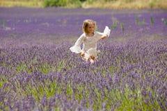 La muchacha rubia hermosa corre a través de un campo de la lavanda Fotos de archivo libres de regalías