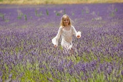 La muchacha rubia hermosa corre a través de un campo de la lavanda Foto de archivo libre de regalías