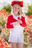 La muchacha rubia hermosa del niño está llevando la guirnalda de las flores rojas en el prado de la amapola, tiempo de primavera Fotos de archivo