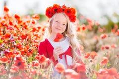 La muchacha rubia hermosa del niño está llevando la guirnalda de las flores rojas en el prado de la amapola, tiempo de primavera Foto de archivo