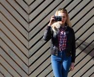 La muchacha rubia hermosa en gafas de sol enormes y una chaqueta negra que plantea el nex al día soleado de madera de la pared ha Foto de archivo